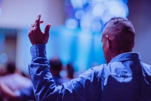 Photo of man praying with hand up